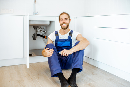 Portrait of a handsome plumber in overalls sitting near the sink at the kitchen