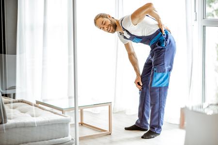 Werkman voelt pijn in zijn rug tijdens het verplaatsen van meubels in de woonkamer thuis Stockfoto