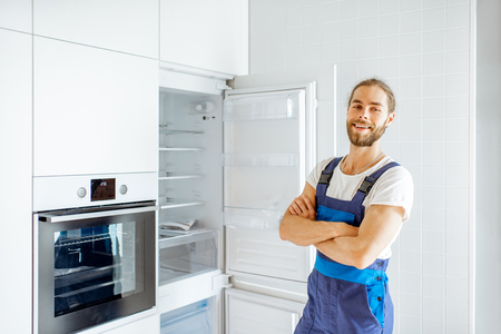 Portrait of a handsome workman installing new refrigerator in the modern kitchen at home