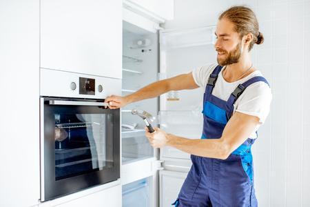 Werkman die thuis de sterkte van de glazen ovendeur controleert met een hamer