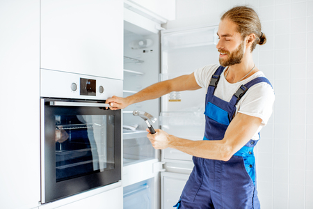 Workman checking the strength of the glass oven door with a hammer at home