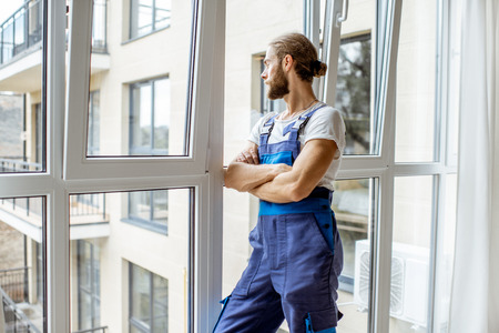 Portrait of a handsome workman in overalls standing near the window in the renovared apartment