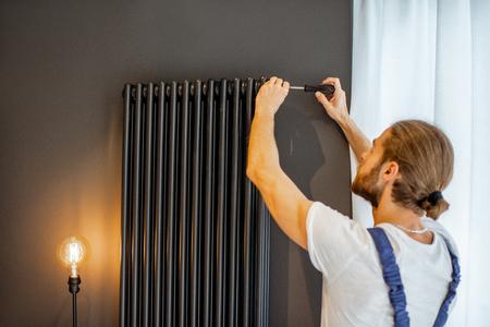 Tuttofare che sgonfia l'aria dal radiatore del riscaldamento dell'acqua a casa