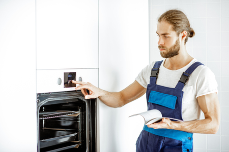 Handsome workman in overalls setting up electric oven on the kitchen at home