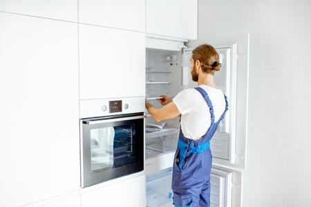 Przystojny robotnik instalujący nową lodówkę w nowoczesnej kuchni w domu