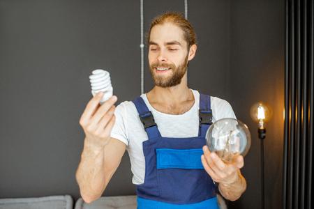 Handyman choosing between energy saving and traditional lightbulb at home