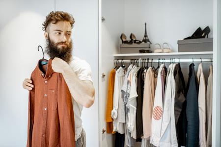 Homme barbu essayant une chemise, choisissant des vêtements à porter dans l'armoire à la maison