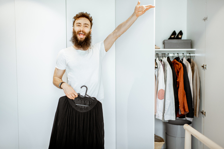 Portrait of a funny and enthusiastic man trying black female skirt in the wardrobe at home