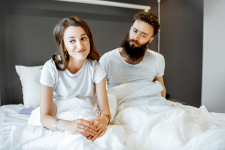 Young couple having problems in intimate relationship, feeling sad while sitting in the bed at home
