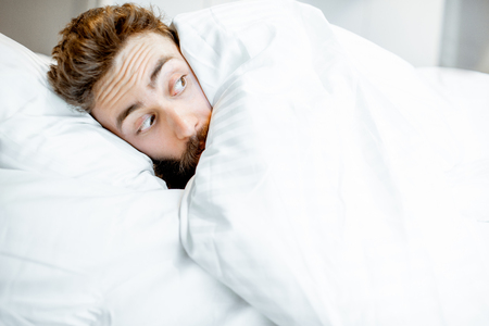 Man hiding in bed under the white sheets feeling scared alone