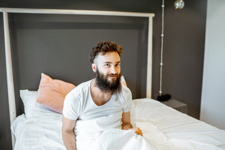 Portrait of enthusiastic bearded man, waking up in the bed, feeling good in the morning Stock Photo