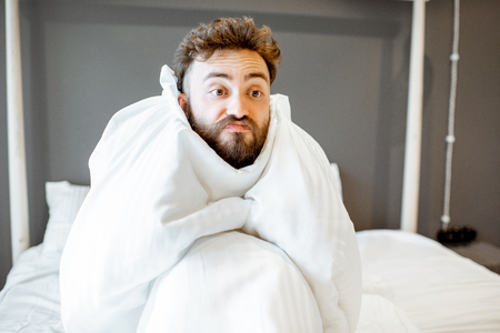 Frustrated man with emotional insanity sitting on the bed covered with white sheets. Concept of insomnia or emotional problems Banco de Imagens