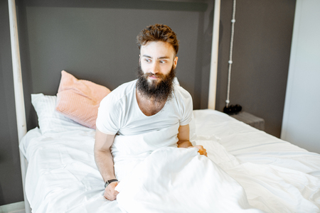Portrait of a bearded man waking up in the bed, feeling frustrated or uncomfortable in the morning Stock Photo