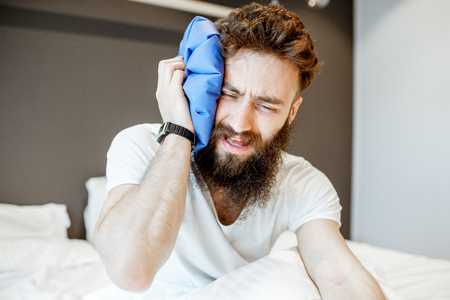 Man feeling bad, sitting on the bed with headache and applying ice bag Stock Photo