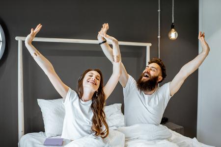 Feliz pareja despertando con las manos levantadas, sintiéndose bien por la mañana en casa