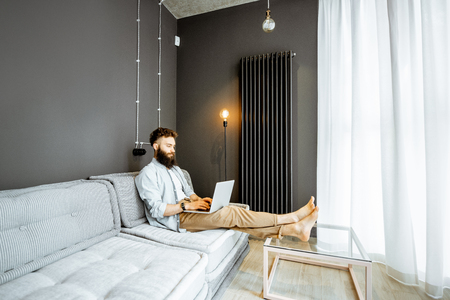 Creative bearded man working with laptop, sitting on the couch in the living room at home