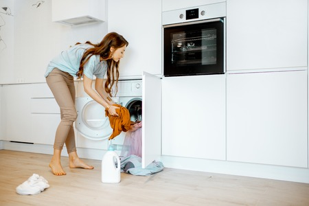 Young woman putting dirty clothes into the washing machine on the kitchen at home