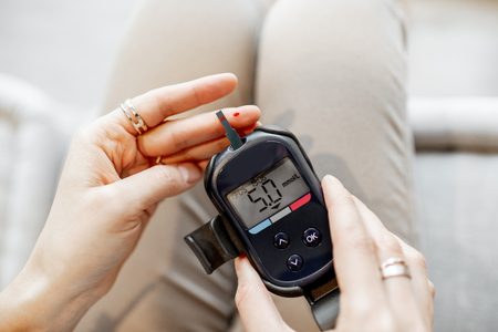 Young woman measuring the level of blood glucose using portable glucometer, close-up view