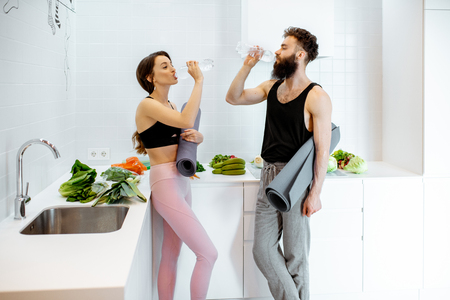 Young couple in sportswear having a break after the yoga training, drinking water at the kitchen with healthy food at home