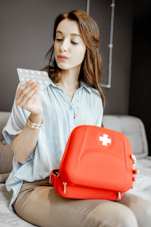 Young woman taking some medicines from the first aid kit, feeling unwell while sitting on the couch at home 写真素材