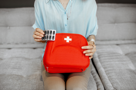 Woman taking pills from the first aid kit, close-up with no face 写真素材