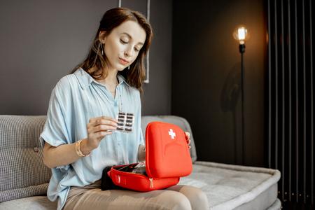 Jeune femme prenant des médicaments de la trousse de premiers soins, se sentant mal alors qu'elle était assise sur le canapé à la maison Banque d'images