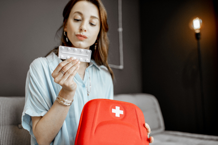 Young woman taking some medicines from the first aid kit, feeling unwell while sitting on the couch at home