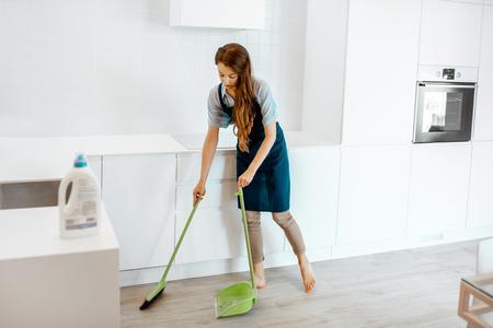 Mujer joven sirvienta limpiando el piso en la cocina de casa