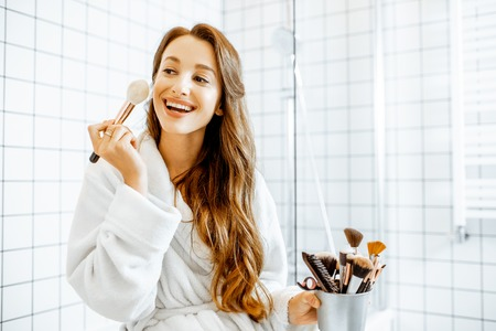 Beautiful woman taking care of herself, applying some cosmetics while sitting on the bathtub in the white bathroom interior