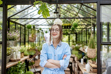 Portrait of a young and confident woman standing at the entrance of the beautiful greenhouse or flower shop