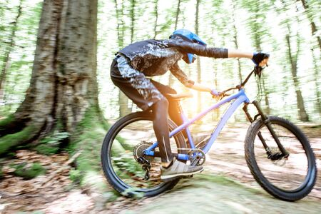Professional well equipped cyclist riding downhill on the off road in the forest. Concept of an extreme sport and enduro cycling. Image with motion blur