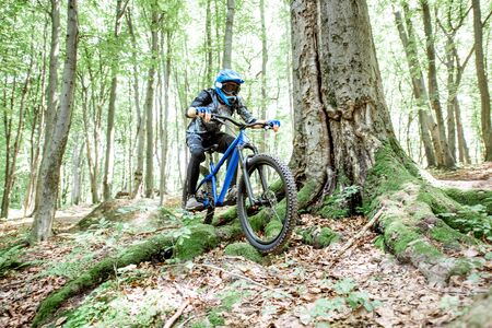Professional well equipped cyclist riding downhill on the off road in the forest. Concept of an extreme sport and enduro cycling