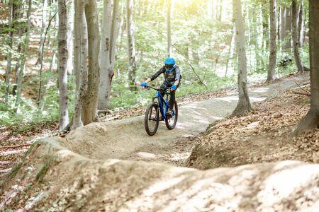 Professionele wielrenner die bergafwaarts rijdt op de mtb-fiets op het bospad. Concept van een extreme sport en enduro fietsen