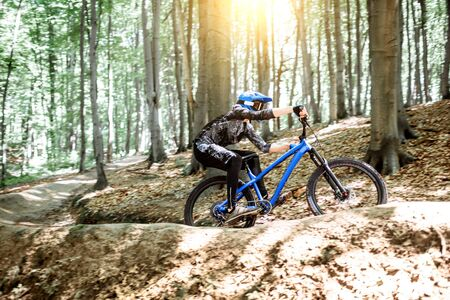 Professional cyclist riding downhill on the mtb bicycle on the forest track. Concept of an extreme sport and enduro cycling