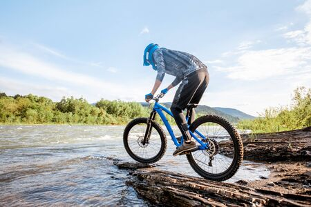 Professional well-equipped cyclist riding on the rocky riverside in the mountains. Concept of a freeride cycling and extreme sport