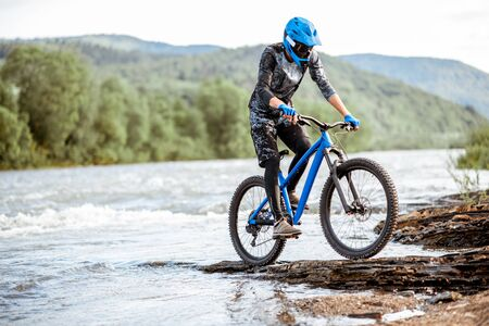 Professional well-equipped cyclist riding on the rocky riverside in the mountains. Stockfoto