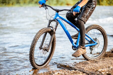 Professional well-equipped cyclist riding on the rocky riverside in the mountains. Close-up with no face
