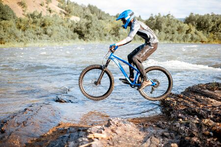 Professional well-equipped cyclist riding on the rocky riverside in the mountains. Concept of a freeride and off road cycling Stockfoto