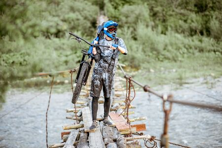 Professional well-equipped cyclist carrying bicycle on the old wooden bridge in the mountains. Concept of a freeride and off road cycling