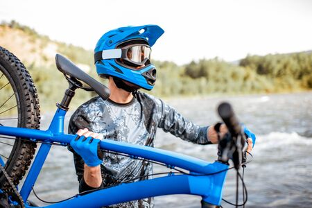 Professional well-equipped cyclist standing with bicycle on the riverside in the mountains. Concept of a freeride and off road cycling