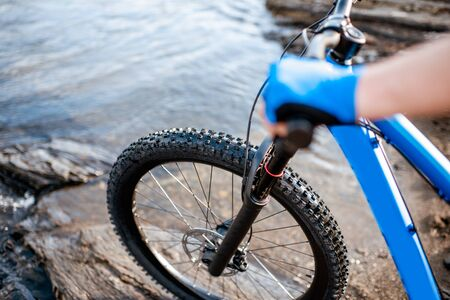 Professional cyclist riding on the rocky riverside in the mountains. Concept of a freeride cycling and extreme sport Close-up view