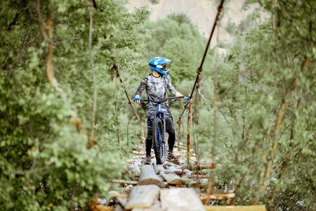 Professional well-equipped cyclist riding on the old wooden bridge in the mountains. Concept of a freeride and off road cycling Stockfoto
