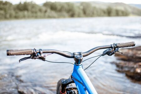 Cycle's steering wheel on the mountain river background. Concept of a freeride and off road trails