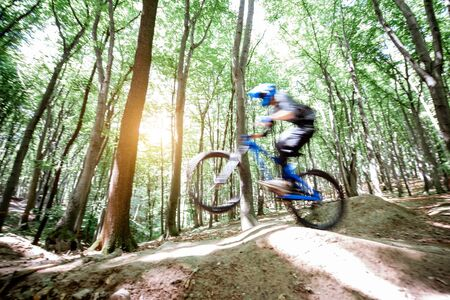 Professional well equipped cyclist riding on the forest track with slides for jumping. Concept of an extreme sport and enduro cycling. Image with motion blur Stockfoto