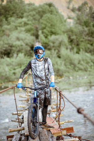 Professional well-equipped cyclist standing with bicycle on the old wooden bridge in the mountains. Concept of a freeride and off road cycling