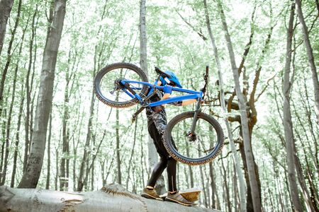 Professional cyclist carrying bicycle while riding off road in the forest. Concept of an extreme sport and enduro riding