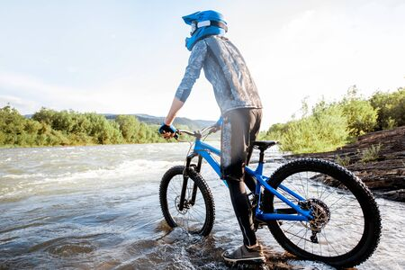 Professional well-equipped cyclist looking forward while standing on the rocky riverside in the mountains Stockfoto