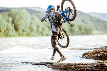 Professional well-equipped cyclist carrying bicycle on the rocky riverside in the mountains. Concept of a freeride cycling