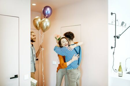 Joyful friends greeting a man with his birthday, hugging and giving presents in the apartment hall near the entrance