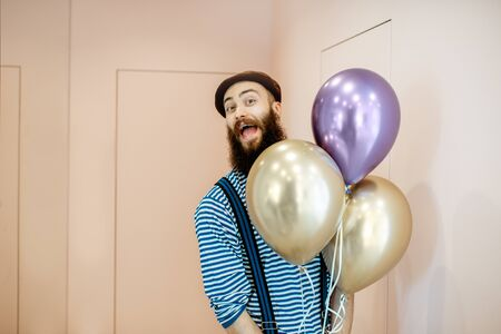 Portrait of a joyful man in festive clothes with balloons coming home for birthday celebration